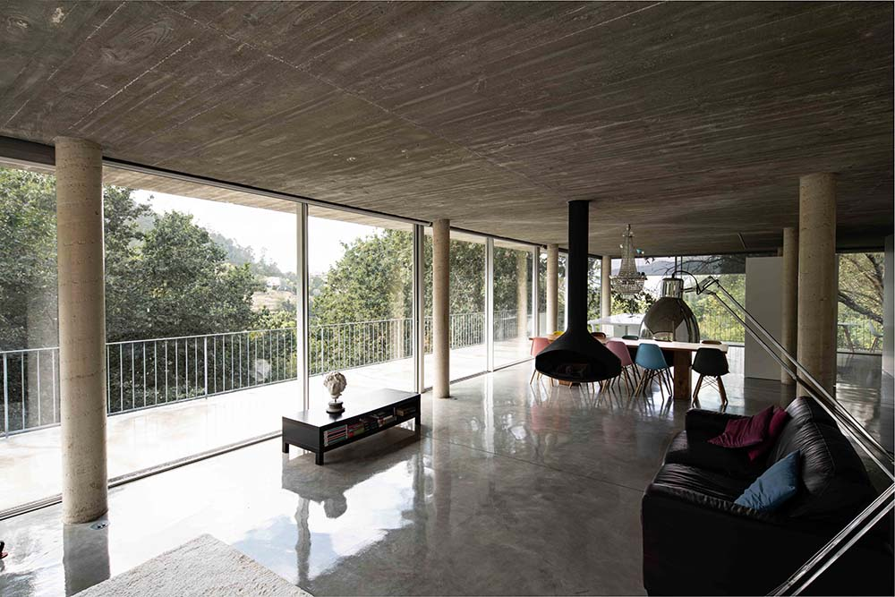 On the far side of the living room is the glass wall and the balcony beyond it with view of the trees.