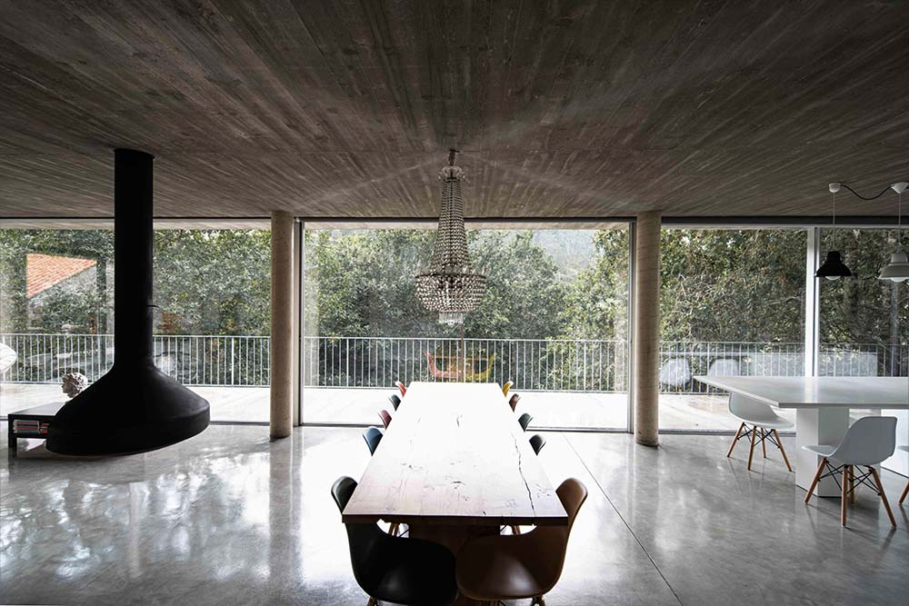 Next to the fireplace is the dining area with a long rectangular dining table surrounded by colorful chairs.