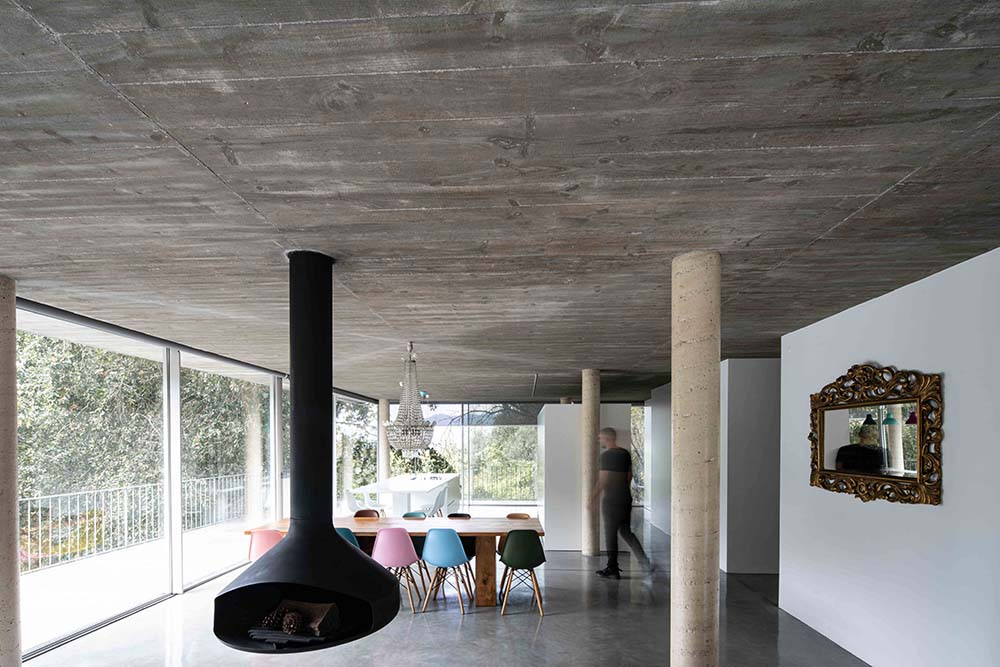 This is another view of the modern black fireplace and its proximity to the dining area.