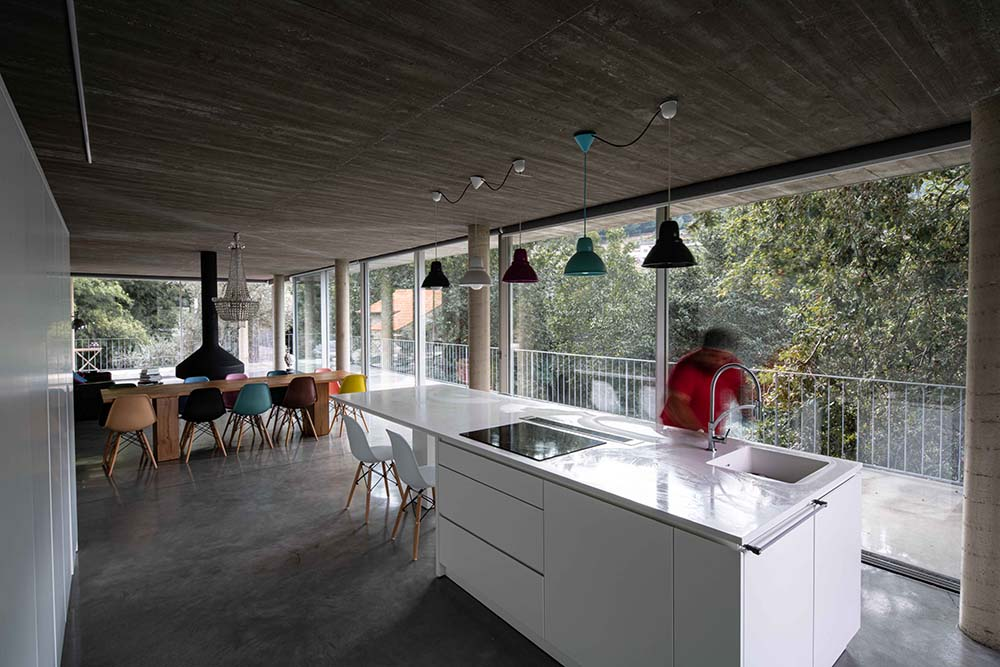 The large white kitchen island is topped with a row of pendant lights hanging from the concrete ceiling.