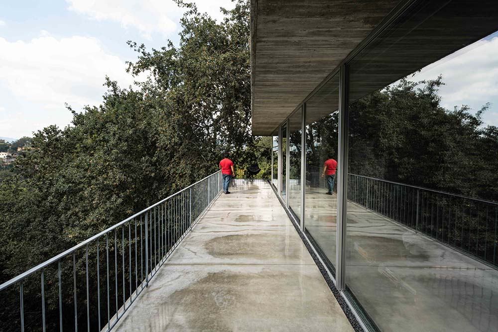 This is a closer look at the balcony outside the glass walls with a concrete walkwaya nd metal rialings.