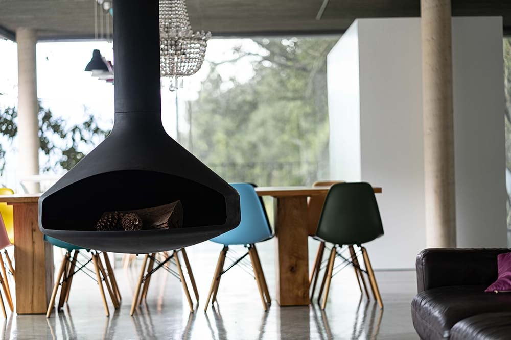 This is another close look at the hanging fireplace with a view of the dining area behind it.