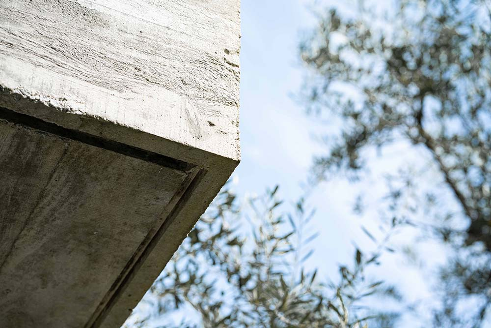 This is a close look at the corner of the concrete balcony complemented by the surrounding thick foliage of trees.