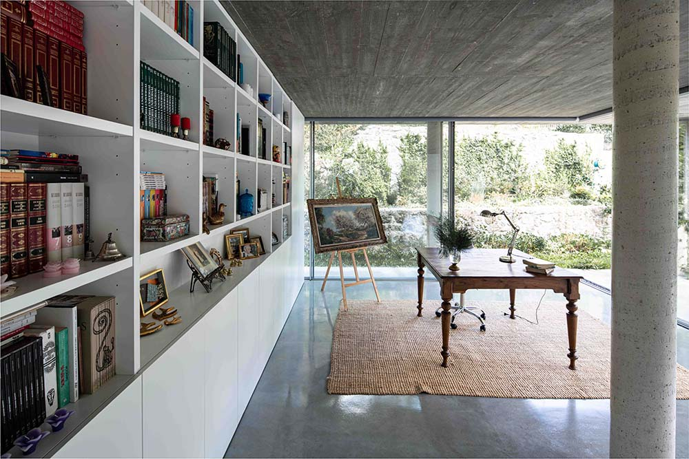 This is the home office with a large white built-in shelf on the wall across from the wooden desk and the glass walls.