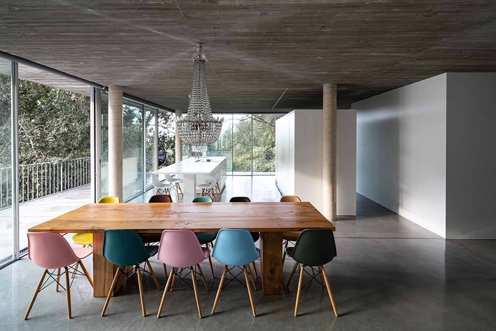 This is another look at the dining area that has a rectangular wooden dining table surrounded by the colorful chairs.
