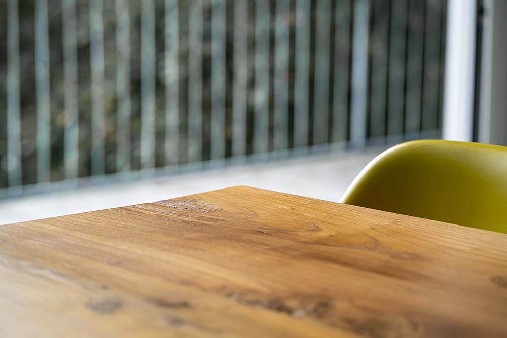 This is a closer look at the wooden dining table and its texture paired iwth modern chairs.