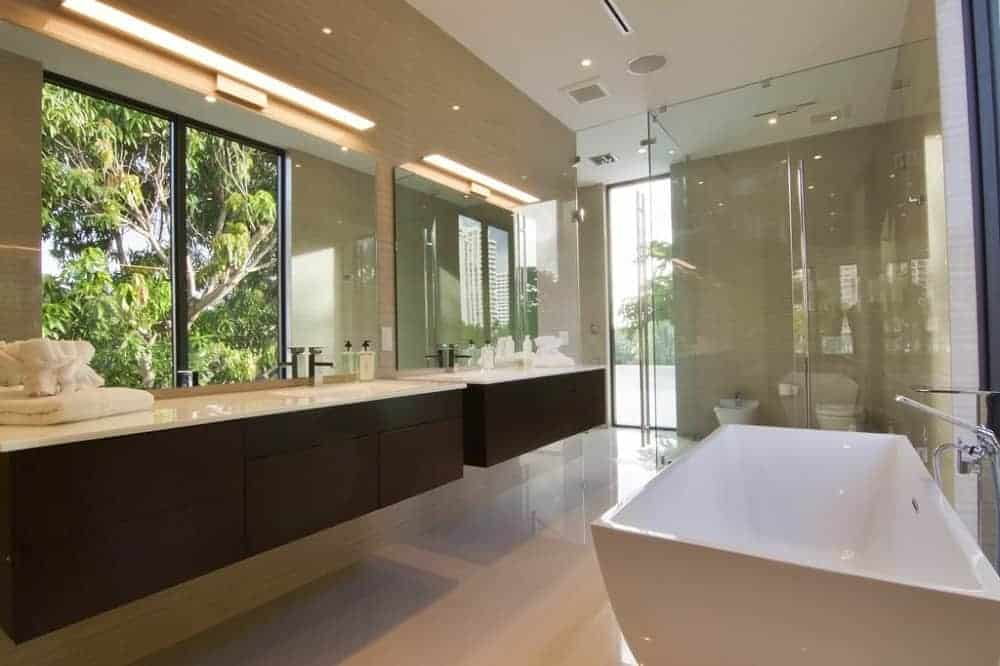 The primary bathroom has a bathtub across from the two-sink floating vanity that has a dark brown tone that contrasts the beige floor and walls.