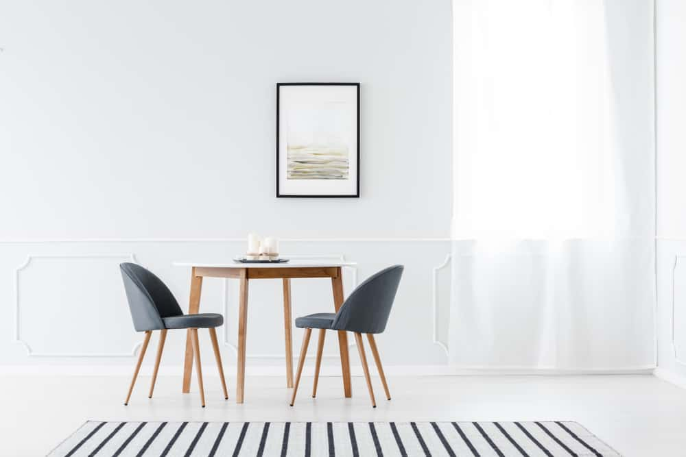 This is a simple and bright dining room with white walls and floor that makes the simple dining set stand out.