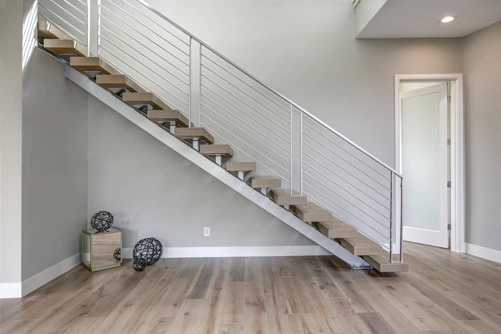 This is a close look at the minimalist foyer with hardwood flooring that matches the steps of the stairs adorned with a few decors underneath.