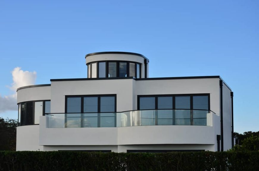 This is a close look at a minimalist house exterior with white walls and an abundance of glass windows.
