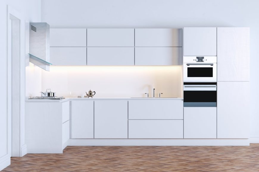 This is a close look at a minimalist modern kitchen with consistent white tones on its cabinetry, counters and backsplash complemented by the flooring.