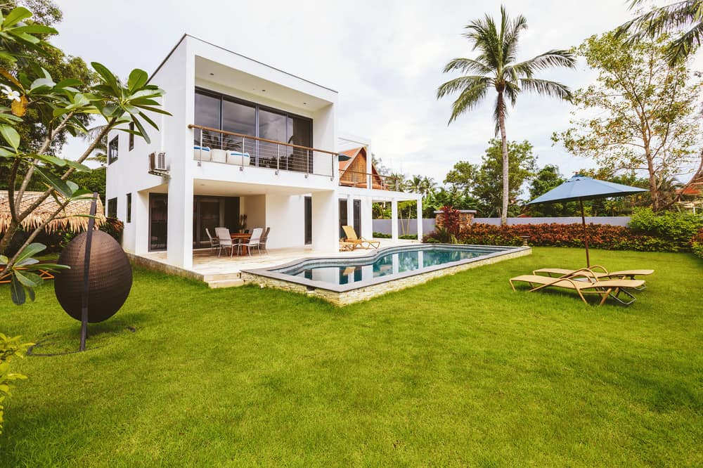 This is a look at the backyard of the house that has a minimalist design along with grass lawns and a swimming pool.