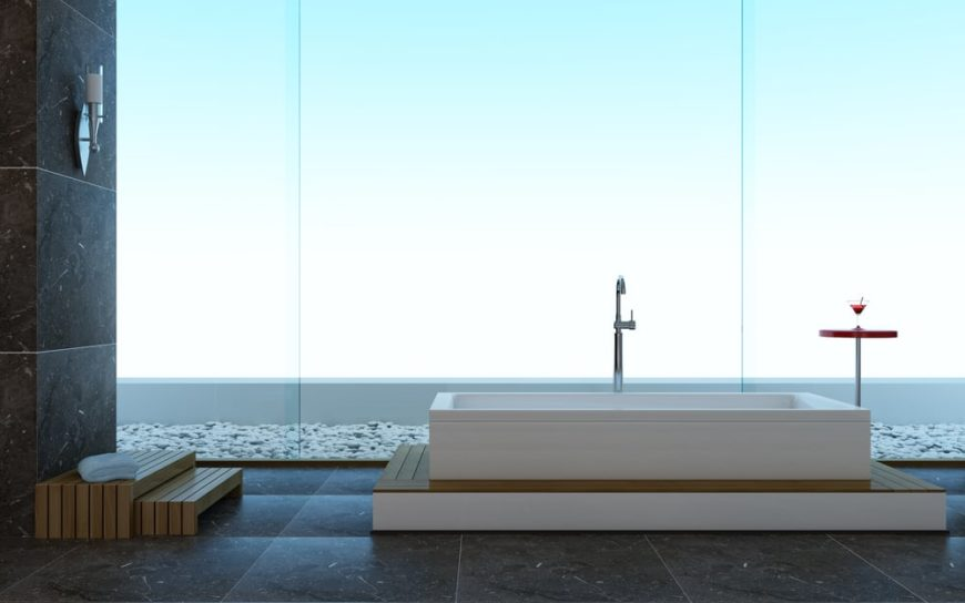 This is a simple primary bathroom with a bathtub by the large glass wall that brightens the gray tiles of the bathroom.