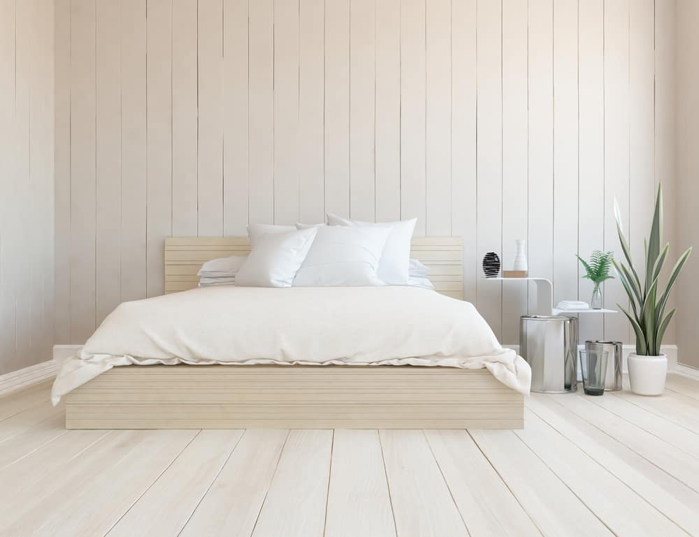 This is a close look at a minimalist bedroom that has a wooden platform bed that matches the surrounding wooden shiplap walls and floor.