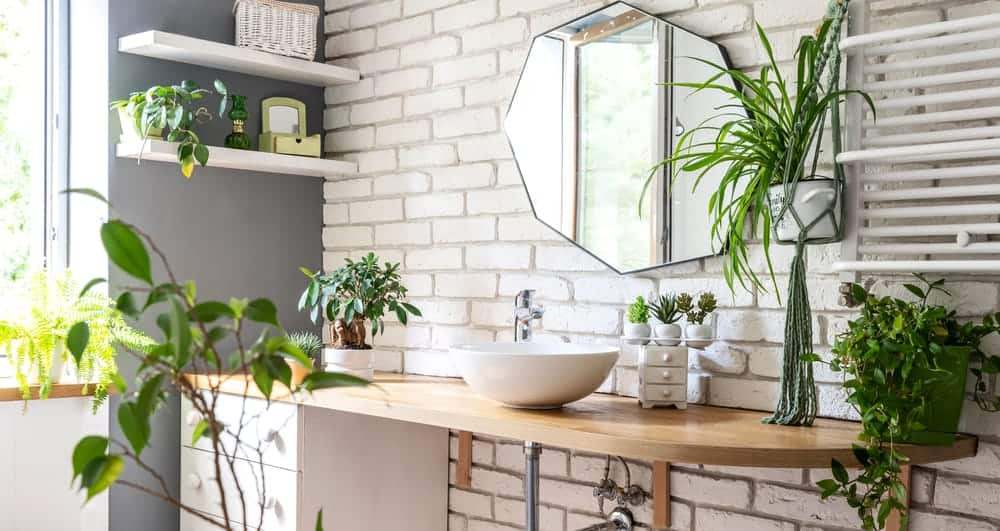 This is a close look at a bathroom vanity area adorned with various potted plants that go well with the white bricks.