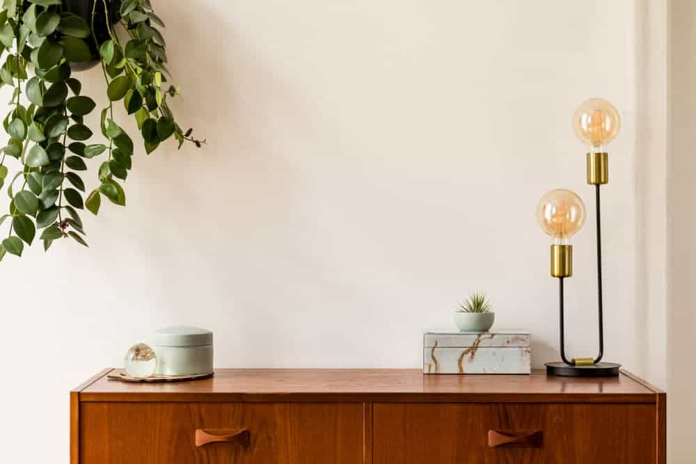 This is a close look at the decors on the wooden console drawer with a simple minimalist lamp that has two light bulbs.