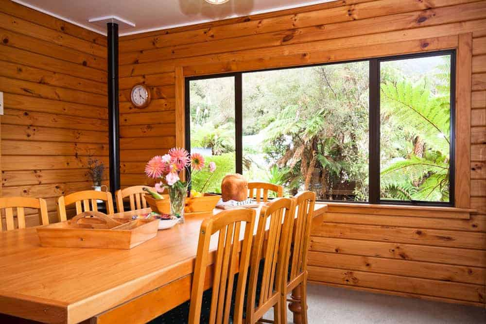 This is a close look at the mountain chalet-style dining room with wooden shiplap walls, large windows and a wooden dining set that matches the tone of the walls.