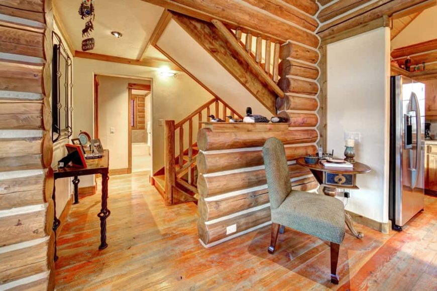 This is a close look at the mountain chalet foyer with wooden log walls, hardwood flooring and small table with a gray chair on the side.