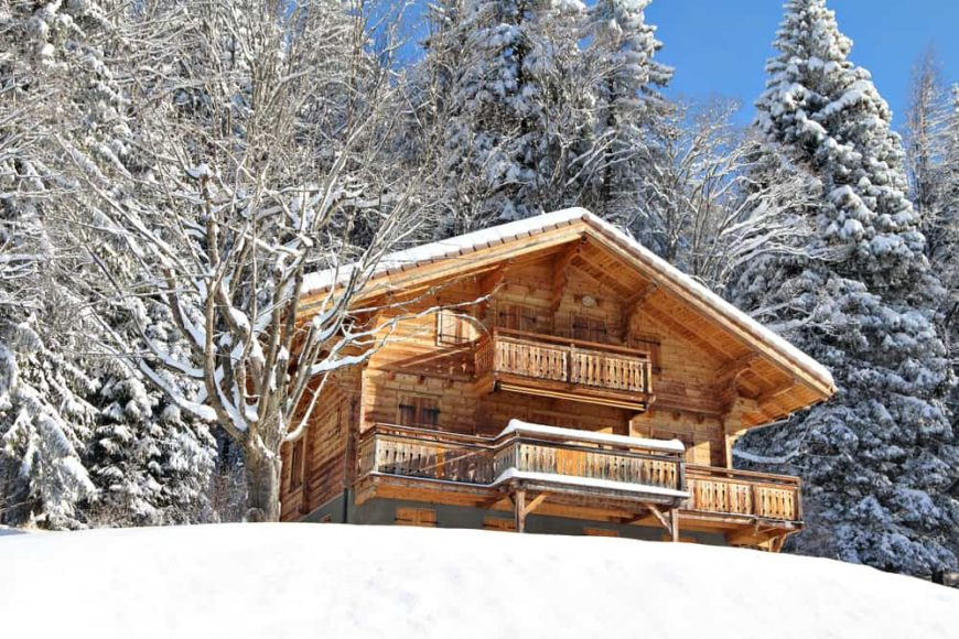 This is a close look at the mountain chalet-style home with wooden exterior walls that stand out against the surrounding snow landscape with tall pine trees in the background.