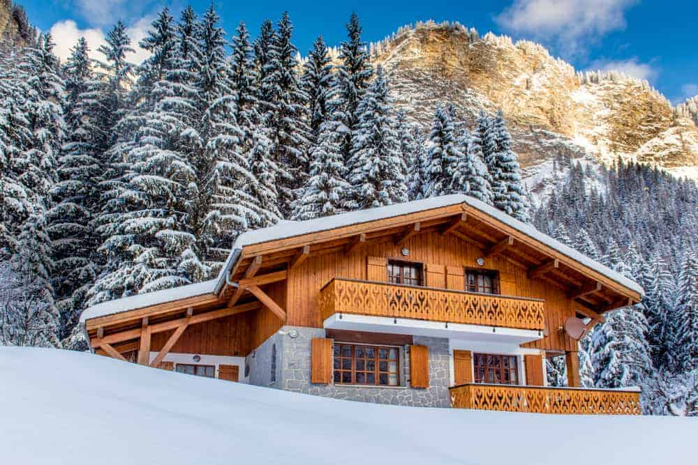 This is an exterior look at the mountain chalet home with wooden shiplap exterior walls, a snowy landscape and a background of tall pine trees.