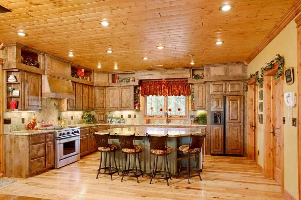 This is a mountain chalet-style kitchen with wooden shiplap walls and ceiling to match the wooden cabinetry lining the walls and the kitchen island. These are then complemented by the multiple recessed lights of the ceiling.