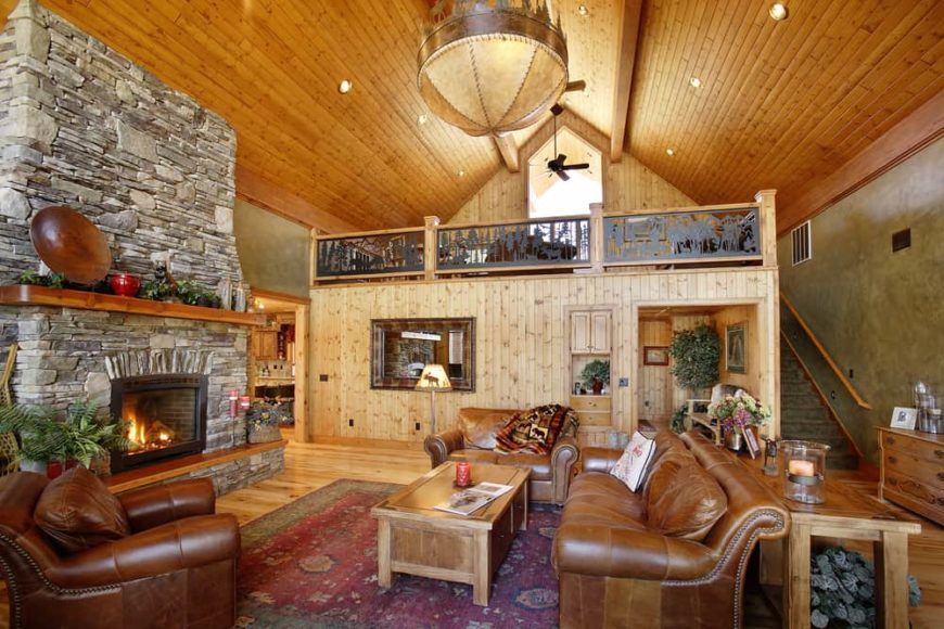 This is a full view of this mountain chalet-style living room with a tall wooden cathedral ceiling, brown leather sofas and a large mosaic stone fireplace across from the wooden coffee table.