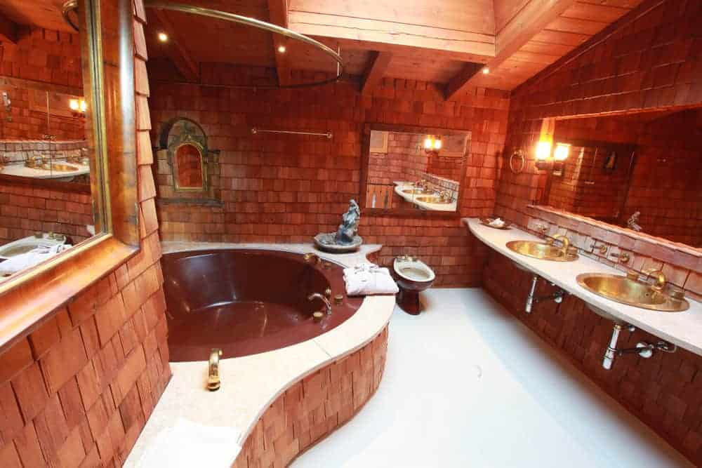 This is a mountain chalet-style bathroom that has wooden shingles and panels on its walls giving it a textured pattern that complementes the bathtub, and floating two-sink vanity,