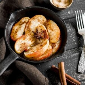 Apple slices with cinnamon in a skillet.