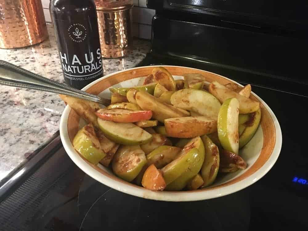 A bowl of freshly-baked apple slices with spices.