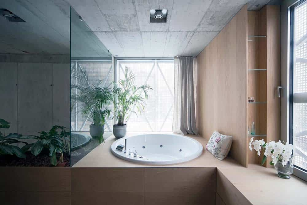 This is a close look at the primary bathroom that has a large wooden structure that houses the round bathtub by the window adorned with a potted plant.