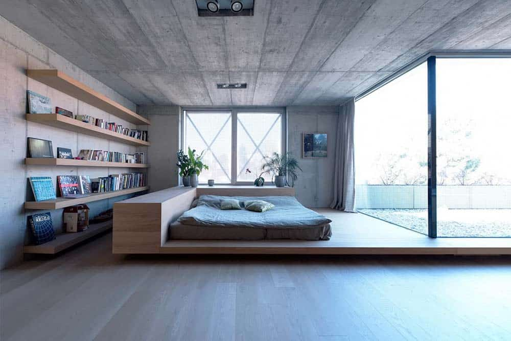 This is a full view of the minimalist bedroom that has a wooden platform bed that matches the wooden floating shelves on the side.