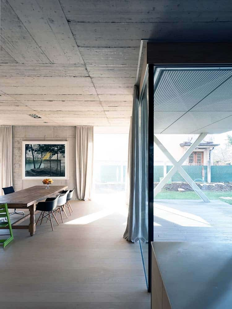 This is a close look at the dining room that has consistent gray concrete walls, ceiling and floor to complement the wooden dining table surrounded by dark chairs.