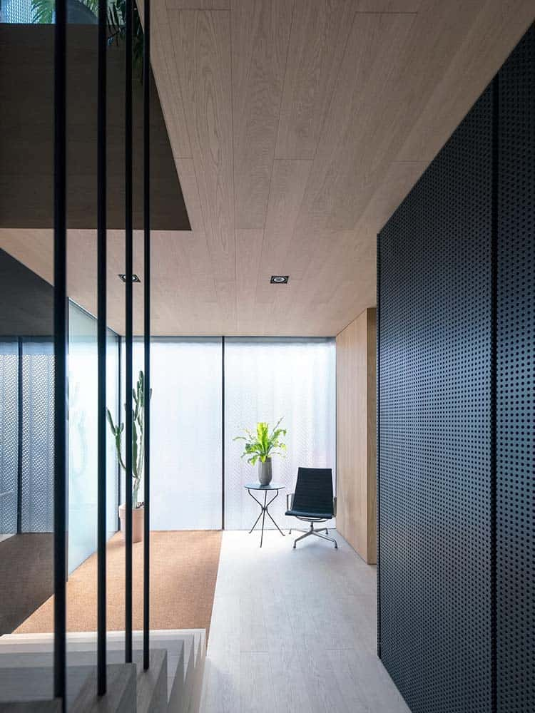 This is a look at the simple minimalist foyer that has a chair and side table along with a potted plant by the side of the main door that has frosted glass walls.