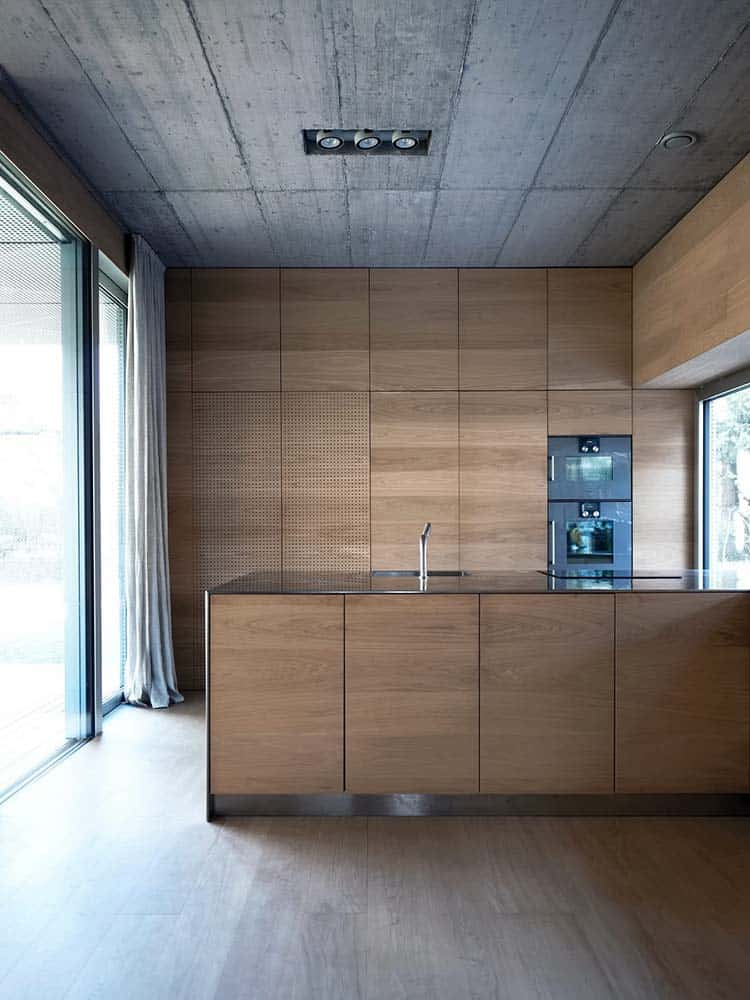 This is a close look at the kitchen that has consistent wooden cabinetry that matches the kitchen peninsula topped with a concrete ceiling.