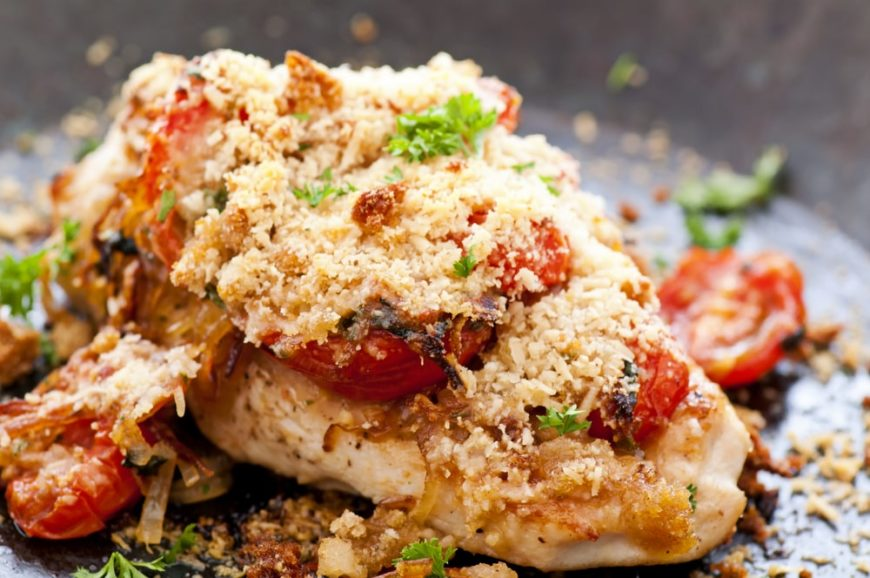 A close look at a piece of parmesan crusted chicken breast on a plate.
