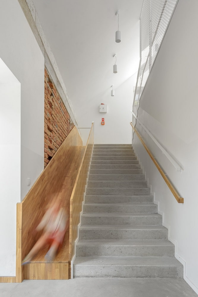 This is a close look at the kindergarten's staircase with a built-in wooden slide on the side.