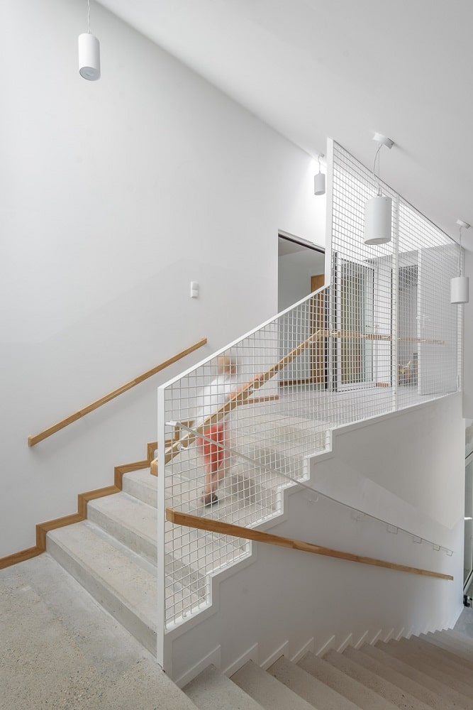 This is a close look at the stairs going to the upper floor with white screen panels and wooden banisters for handle.