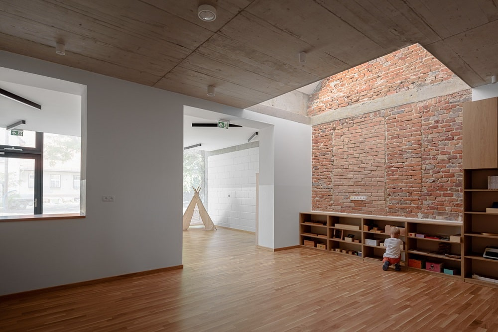 This other classroom has a built-in waist-high wooden shelves by the brick wall on the far side.