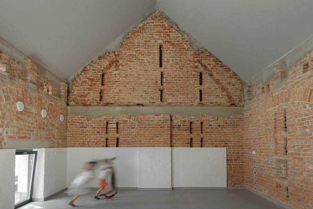This is another upper floor classroom with a tall cathedral ceiling complemented by the textured brick walls.
