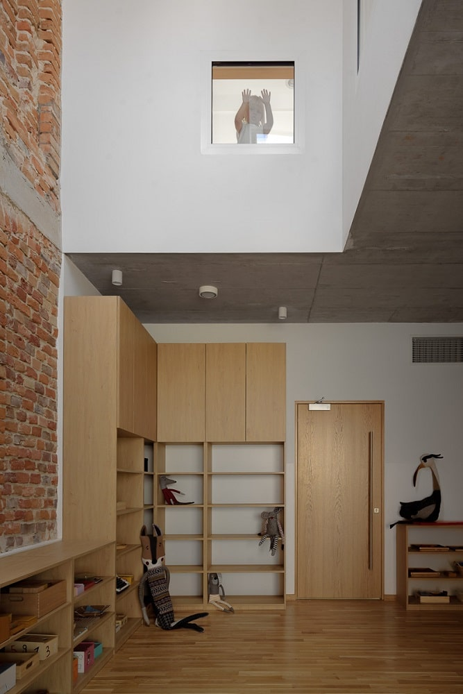 This is a close look at the classroom that has built-in wooden shelves lining the walls. These are then complemented by the tall ceiling and the brick wall.