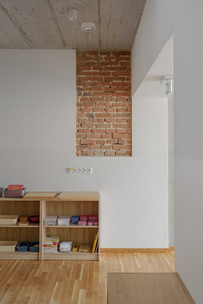 This is a closer look at the low wooden shelf by the entryway adorned with a piece of exposed red brick wall panel.
