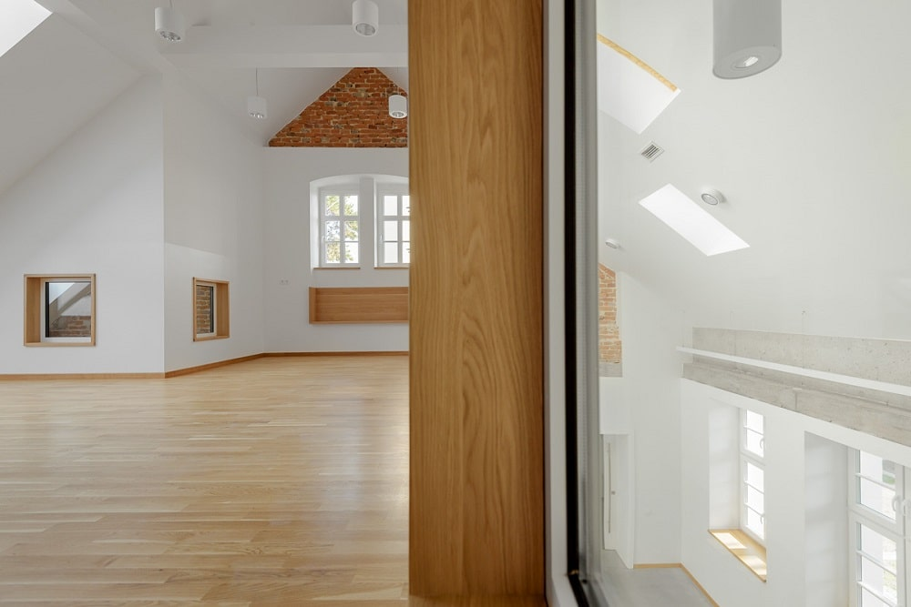 This is a close look at the glass window looking down onto the classroom below and the large wooden pillar beside it.