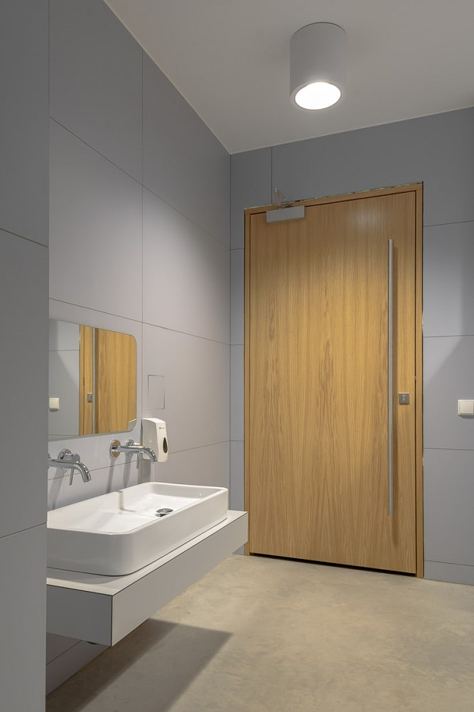 This bathroom has a wooden door, white porcelain sink and concrete walls.