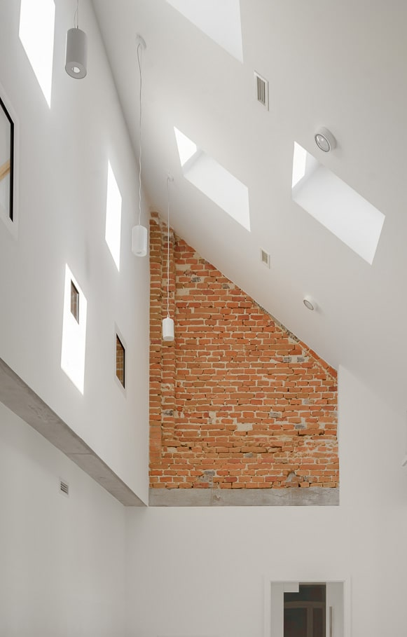 This is a look at the top of the classroom with a large brick exposed wall and a couple of skylights.