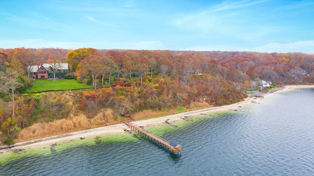 This is an aerial view of the whole property showcasing the large mansion, the landscaping of grass lawns, the boat dock and the surrounding tall trees. Image courtesy of Toptenrealestatedeals.com.
