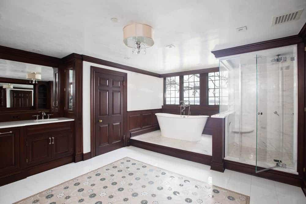 This is a close look at the primary bathroom with bright beige and dark wooden tones that make the bathtub stand out as well as the glass-enclosed shower area beside it. Image courtesy of Toptenrealestatedeals.com.