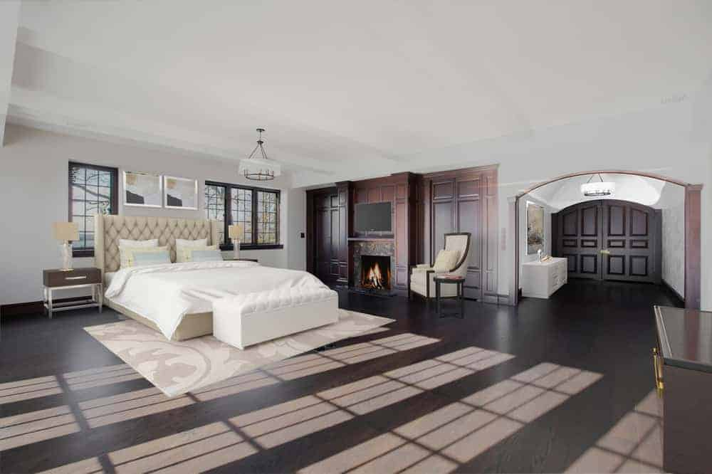 This is the spacious primary bedroom that has a large white bed on the far wall. Beside it is a paneled wall that houses the fireplace to match the hardwood flooring. Image courtesy of Toptenrealestatedeals.com.