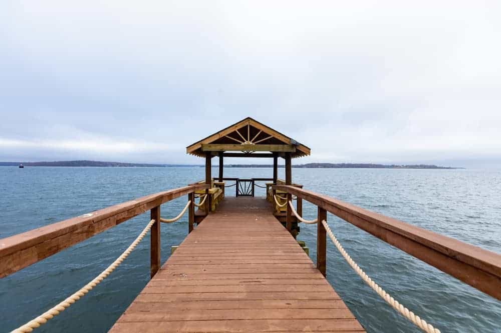 This is a close look at the wooden walkway to the boat dock at the far end with a view of the sea. Image courtesy of Toptenrealestatedeals.com.