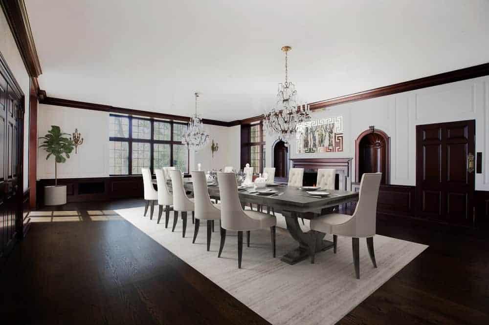 Une salle à manger formelle avec un spacieux plancher, une grande cheminée et une grande table à manger surmontée de deux grands lustres et entourée de chaises. ©Toptenrealestatedeals.com