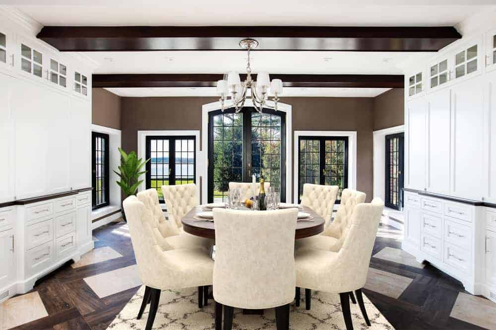 This is the informal dining area and breakfast nook with beige cushioned chairs surrounding the wooden table topped with a small chandelier and surrounded by large windows that bring in natural lighting. Image courtesy of Toptenrealestatedeals.com.